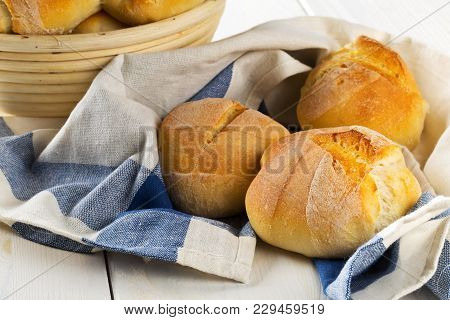 Bunch Of Whole, Fresh Baked Wheat Buns In Baking Basket And On Kitchen Towel On White Wooden Table