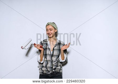 Smiling Young Girl In A Plaid Shirt Painting The Walls Using A Platen In White