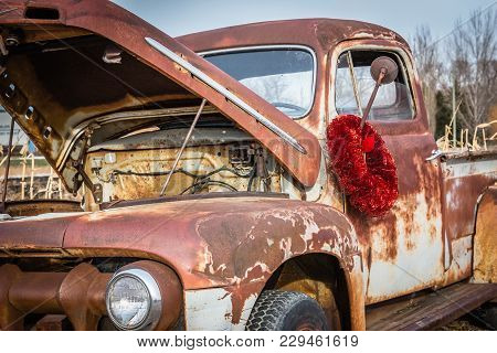 Extreme Close Up Horizontal Image Of An Old Rusted Truck With A Red Christmas Wreath Hanging Around