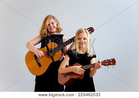 A Portrait Of Two Girls Playing Guitar