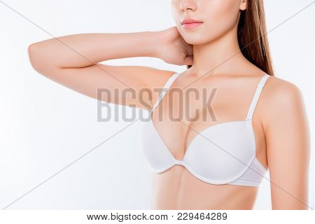 Cropped Close Up Photo Of Beautiful Woman's Breast Clothed In White Classic Bra Cups She Is Touching
