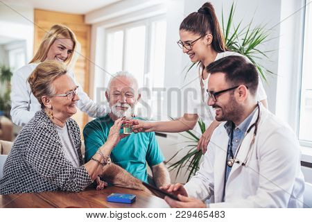 Senior Couple In Discussion With Health Visitor At Home. They Talk About Prescribed Therapy And Givi