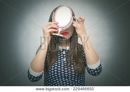 Woman Girl Looks In The Mirror, Does Make-up And Pretties Isolated On Gray Background. Getting Ready
