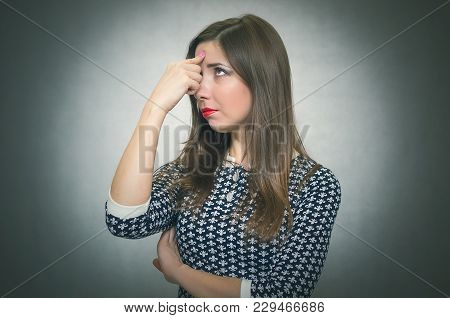 Pensive Wistful Woman Is Wondering And Thinking Isolated On Gray Background. Worried Girl.