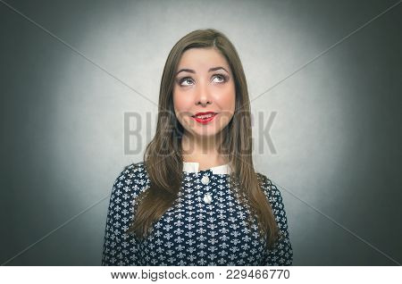 Happy Wistful Woman Is Dreaming And Wondering Isolated On Gray Background.
