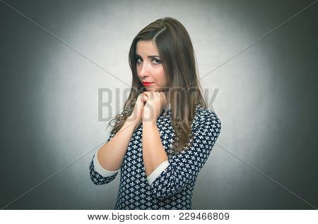 Pensive Modest Woman. Shy Girl Concept Isolated On Gray Background.