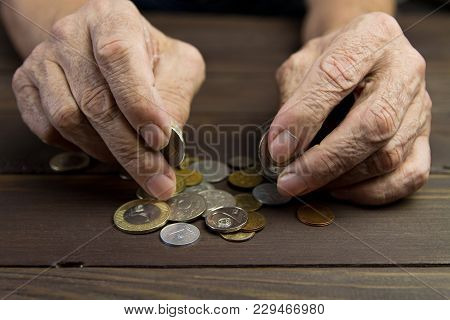 Hands Of Beggar With Few Coins. The Concept Of Poverty . An Elderly Person On Pension Holds Coins On