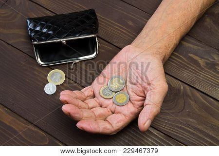 Hands Of Beggar With Few Coins.  An Elderly Person Holds The Coins Over The Old Empty Wallet. The Co