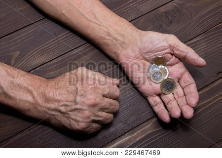 Begging For Money. Elderly Person Hands Of Beggar With Few Coins. The Concept Of Poverty