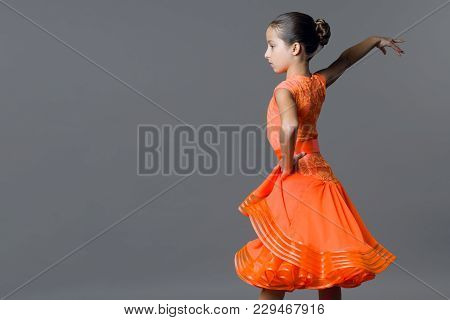 Portrait Of A Girl Child 9-10 Years Old Dancer. Sports Ballroom Dancing, Latino. Girl In An Orange D