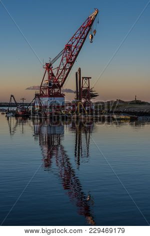Marine Floating Crane Reflected In Calm Water Of The Cove In The Early Hours Of Dawn.