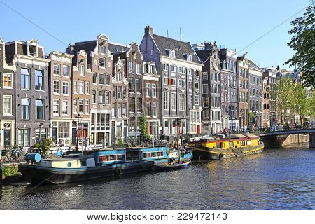 Amsterdam, Netherlands - May 8,2016:old Houses Of Traditional Architecture And Houseboats Along Cana