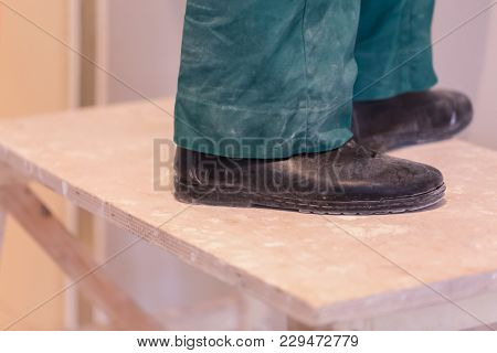 Legs Of Worker With Green Workwear And Black Shoes On The Wooden Stepladder. Worker Makes Plasterboa