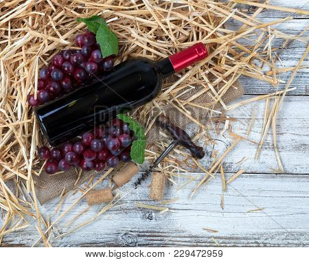 Overhead View Of A Red Wine Bottle, Grapes Plus Corkscrew With Straw And Burlap On White Rustic Boar