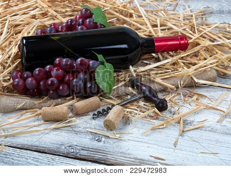 Close Up View Of A Red Wine Bottle, Grapes Plus Corkscrew With Straw And Burlap On White Rustic Boar