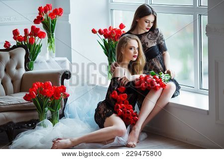 Fashion Models In Tender Black Lingerie Posing In Sensual Way At Luxury Interior Full Of Tulips. You
