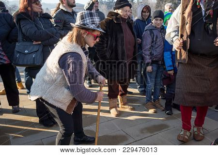 Pernik, Bulgaria - January 26, 2018: Teenage Girl With Hat, Wooden Stick And Red Glasses Surrounded