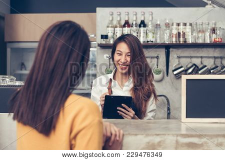 Close Up Of Young Asian Female Coffee Shop Owner Taking The Order From Her Client With A Warm Welcom