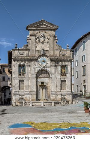 The Old Fountain Of Piazza Del Mercato With The Ancient Artistic Clock Tower In The City Of Spoleto,