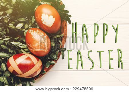 Happy Easter Text On Stylish Easter Eggs And Green Leaves On White Wooden Background Flat Lay. Moder