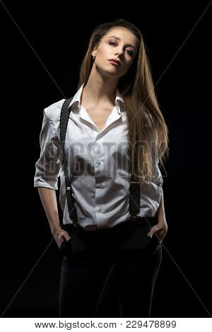 A Young Girl In A Shirt With Suspenders, Impudent And Independent.