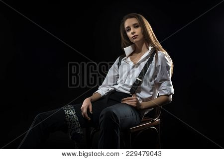 A Young Girl In A Shirt With Suspenders, Impudent And Independent. Sits On A Chair.
