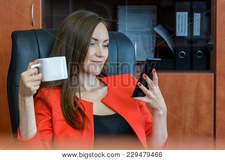 Front View Portrait Of A Young Woman In A Red Business Suit Sitting In A Leather Chair Drinking Coff