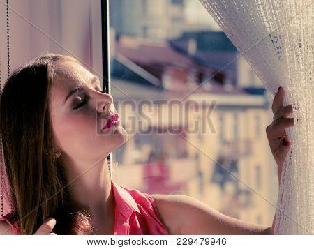 Young Woman Sitting On Windowsill Looking Through Window Enjoying Her Free Time, Relaxing.