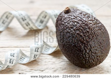 Fresh Organic Avocado Haas  And Measuring Tape On Old Wooden Table Close Up. The Concept Of Diet Foo