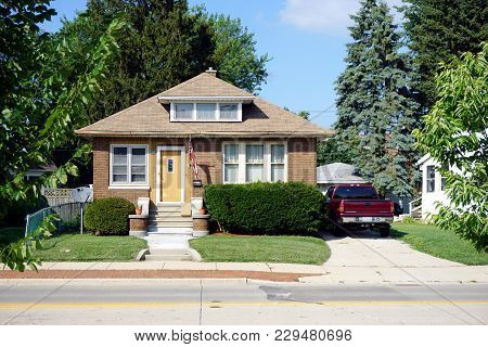 Joliet, Illinois / United States - July 27, 2017: A Small, Brown Brick, Single Family, Cape Code Sty