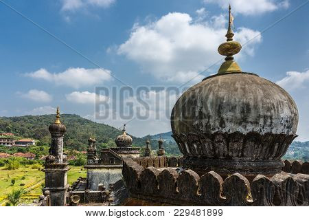 Madikeri, India - October 31, 2013: Domes, Golden Flags And Turrets On Top Of Two Royal Mausolea At