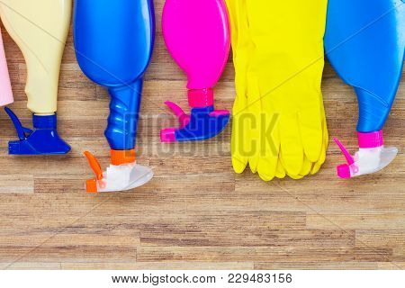 Spring Cleaning Concept - Colorful Sprays Botles And Rubbers On Wooden Background