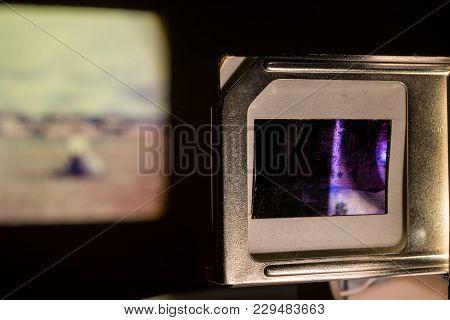 Vintage Photo Slides Projector Showing Old Photographs Slides In Dark Room