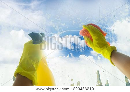 Spring Cleaning - Someones Hands In Yellow Gloves With Spray And Ruber Cleaning Window, Spring Blue