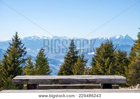Panoramic Snowy Landscape Scenic View From Wooden Bench From Summit Of Mountain Rennfeld And Distant