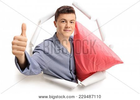 Teenage boy in pajamas with a pillow breaking through paper and making a thumb up sign
