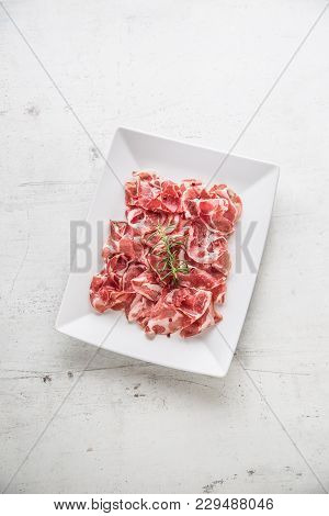 Prosciutto. Curled Slices Of Delicious Italian Prosciutto With Rosemary