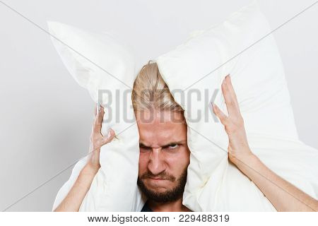 Stressful Unpleasant Situation Conflict. Angry Mad Young Man Closing Ears With Pillows, Protecting F