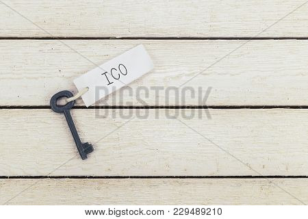Key And Keyring With The Word Ico Over White Wooden Table