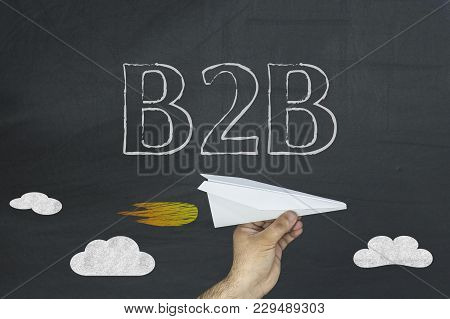Business To Businss B2b Concept On Blackboard. Hand Holding Paper Plane