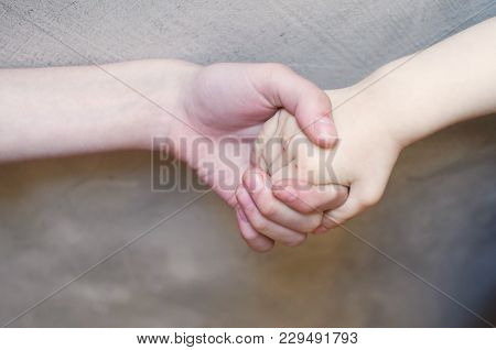 Handshake Of Child Boy And His Older Sister On Blure Grey Brown Wall Background. Hold Your Arm To Pr