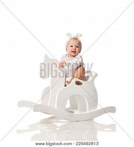 Toddler Baby Girl Is Riding Swinging On A Rocking Chair Toy Horse Over White Background