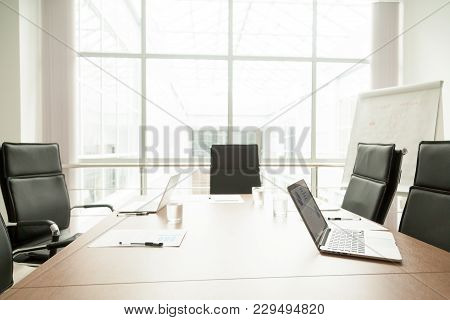 Conference Table With Laptops, Documents And Chairs In Office Of Modern Contemporary Business Center
