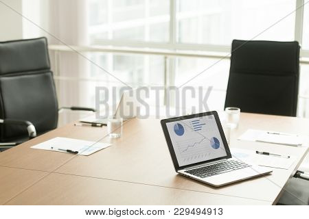 Conference Table For Meeting In Boardroom With No People And Project Statistics Report Graphs Charts