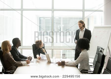 Businessman Gives Presentation Of New Marketing Plan To Multiracial Partners At Boardroom Briefing,