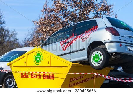Fuerth / Germany - March 4, 2018: A Car Lies In A Trash Container. German Word Diesel- Umweltpraemie