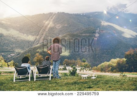 View From Behind Of Group Of Three People Observing Summer Mountains Scenery From The High Point: Tw
