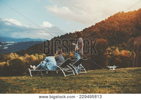 Autumn Scenery With The Group Of Three Friends Of Different Races And Gender Chilling On The Flank O
