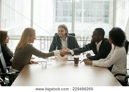 African Businessman And Caucasian Businesswoman Shaking Hands Over Conference Table At Multiracial G