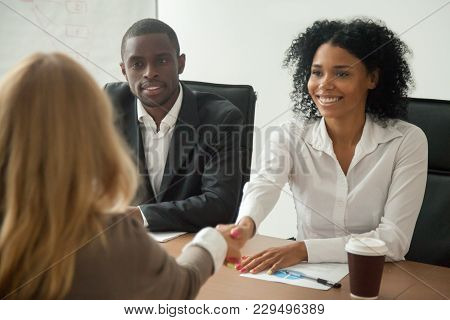 African American Hr Team Welcoming Female Applicant At Job Interview, Diverse Businesswomen Shaking